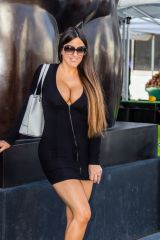 Claudia Romani Showing cleavage in a little black dress while out grocery shopping in the farmers market in Miami