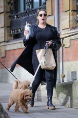 Kelly Brook Cuts a low-key figure as she tucks into a crepe while walking her beloved Cavapoo puppy Teddy in Hampstead