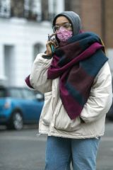 Naomi Ackie Takes a phone call as she seen wrapped up against the near zero degrees weather in London