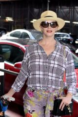 Christina Hendricks Tries power clashing in a checked shirt and floral pants as she walks her dog through Midtown Manhattan