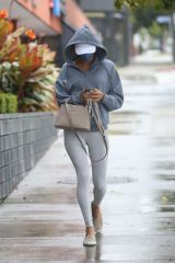 Alessandra Ambrosio Covers her head with a hoody as she goes to a pilates class on a rainy day in Los Angeles