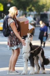 Jane Krakowski Has her hands full with a big box and a pretzel while petting a dog in Manhattan