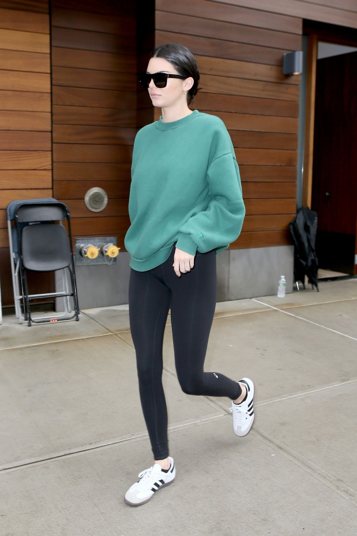 Kendall Jenner Steps out wearing black leggings and a green sweatshirt in NYC