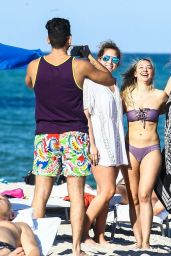 Corinne Olympios Is wearing a purple bikini that shows off her figure on the beach in Miami Beach