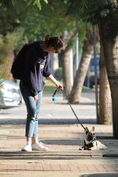 Mia Goth Has trouble walking her french bulldog thru a parking lot