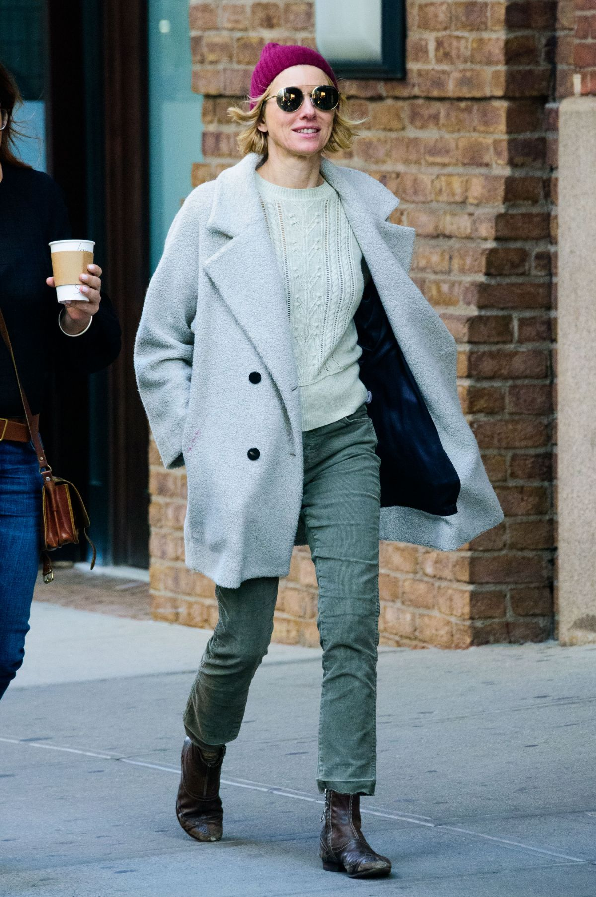 Naomi Watts Wears A Cable Knit Sweater Light Grey Pea Coat And Purple Beanie As