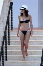 Bethenny Frankel Wears a black bandeau bikini with colorful trim as she relaxes by the pool in Miami