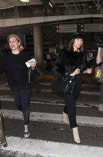 Olivia Culpo Wearing a furry black crop top and black captain hat making her way through LAX in Los Angeles