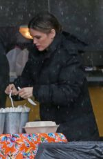 Rachel Bilson Grabs her lunch at the crafty table protected from the torrential rain in Vancouver