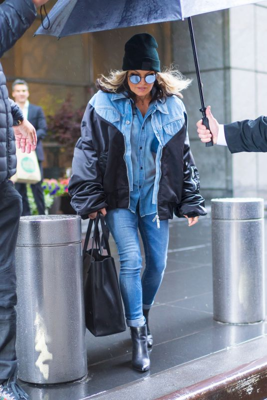 Fergie Wearing all denim and attempting to stay dry under umbrellas as she leaves her hotel in New York City