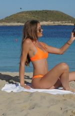 Georgie Clarke In a teeny orange bikini at the beach in Ibiza