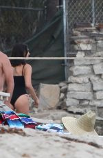 Nina Dobrev In a black one piece bathing suit on the beach in Malibu