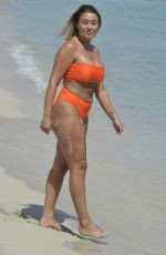 Ellie Young Shows off cleavage in bright orange bikin on the beach in Magaluf
