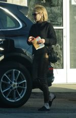 Emma Roberts Sports a pair of leopard print pants as she mails some packages in Los Angeles
