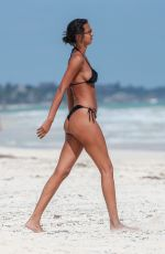 Lais Ribeiro Shows off her fit figure in a black bikini while enjoying a drink and smoke break on the beach in Tulum