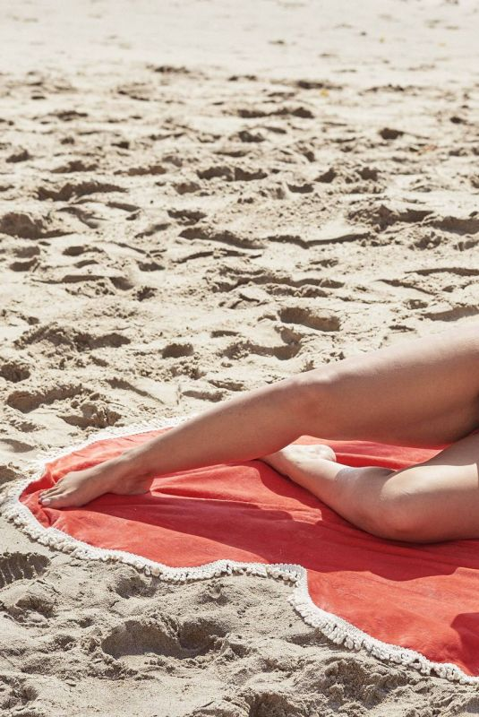 Ashley Graham Showing off her new swimwear collection on a heart-shaped Towel