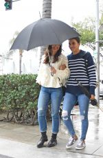 Minka Kelly Share an umbrella with a friend on a rainy day in Los Angeles