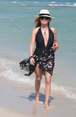 Ramona Singer Wears a low cut black swimsuit on the beach in Miami