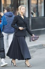 Rose Bertram Wears an ankle length pleated skirt and carries a Dior handbag as she leaves her hotel in Paris