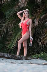Jules Liesl Models a red one piece on the beach while shooting an advert for 138 Water in Malibu