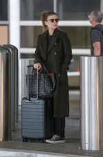 Kate Mara Hides her baby bump under a large green coat arriving at LAX after a trip to Paris for fashion week