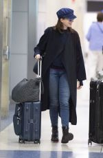 Anne Hathaway Pushes her own luggage as she arrives for a flight at JFK Airport in NYC