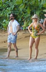 Katy Perry Poses on a beach in a red swim suit as she shoots a new music video in Hawaii