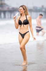 Rachel McCord Cools off with an ice cream while she poses for pictures in a little black bikini in Santa Monica