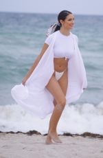 Tao Wickrath Wears a flowing white swimsuit on Miami Beach