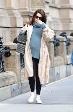 Anne Hathaway Cradles her growing baby bump while on the way to the park in New York City
