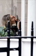 Megan McKenna Applying to make up and false eyelashes before filming inside an office in central London