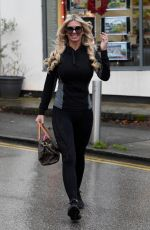 Christine McGuinness Sheltering her new hair doo from the rain