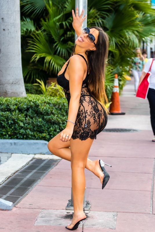 Claudia Romani Poses for photos on the street in a completely sheer dress in Miami