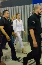 Margot Robbie Is surrounded by her security guards as she arrives in Sao Paulo