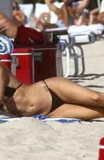 Kimberley Garner Showcasing her toned figure while lounging on the sand in sunny Miami Beach