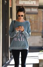 Alessandra Ambrosio Checks her phone on her way in and out of a day spa in LA