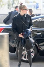 Lucy Boynton In a black denim jacket and floral mini-dress as she leaves LAX airport in Los Angeles