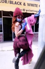 Phoebe Price Poses up in a purple ensemble with a surgical mask and gloves in West Hollywood
