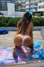 Claudia Romani Poses next to an Easter Bunny in her building in Miami