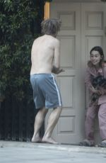 Emilia Clarke In pyjamas cradling her dog while joining clap for NHS workers with topless mystery man in London