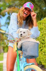 Kelly Bensimon Plays with her dog Fluffy while on a bike ride as she keeps busy at home in West Palm Beach