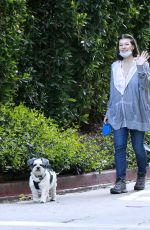 Milla Jovovich Gives a wave and flashes a smile while walking her dogs in Los Angeles