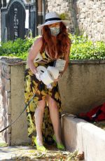 Phoebe Price Poses with a few rolls of toilet paper wearing a floral print dress