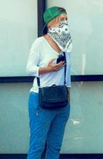 Felicity Huffman Wears a bandana as a face mask as she waits in line in front of a supermarket in Los Angeles