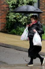 Helena Bonham Carter Gets caught up in the rainy weather and struggles with few bags of groceries while out and about in London