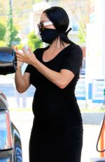 Nikki Bella Displayed her growing baby bump while pumping gas at her local 76 gas station in Studio City