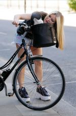 Caprice Taking her poorly pet chihuahua out for a ride on her bike for some fresh air in London
