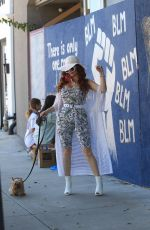 Phoebe Price Poses next to a BLM mural showing support for George Floyd in Los Angeles