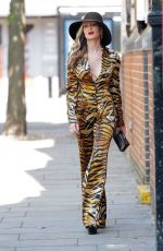 Caprice Goes braless in a plunging tiger print power suit as she walks to a business meeting in London