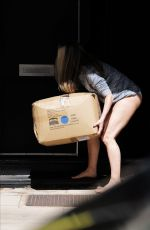 Caprice Shows off her long lean legs and flashes her knickers as she takes deliveries of heavy boxes in London